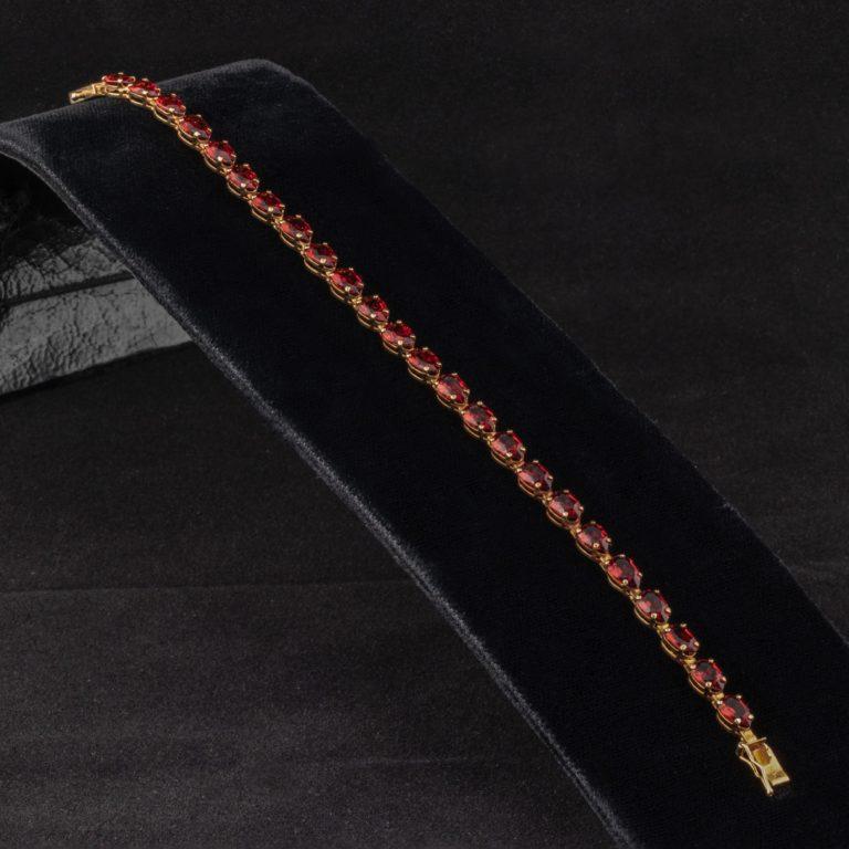 Photo of a red ruby bracelet placed on a black velvet display holder.