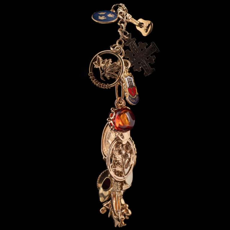 Photo of a 14K gold charm bracelet with an assortment of charms such as a guitar, amber turtle, Canada with leaves symbol, a hat, a shovel, and more.
