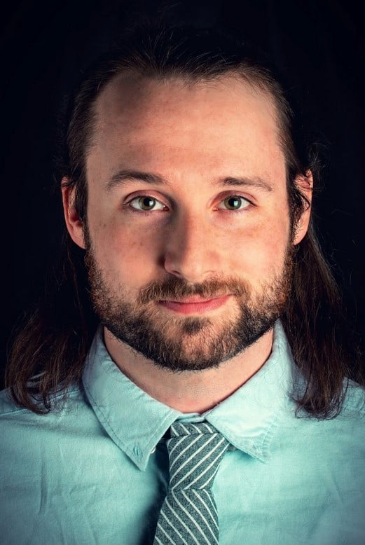 Headshot photo of a gentleman with long brown hair smirching into the camera.