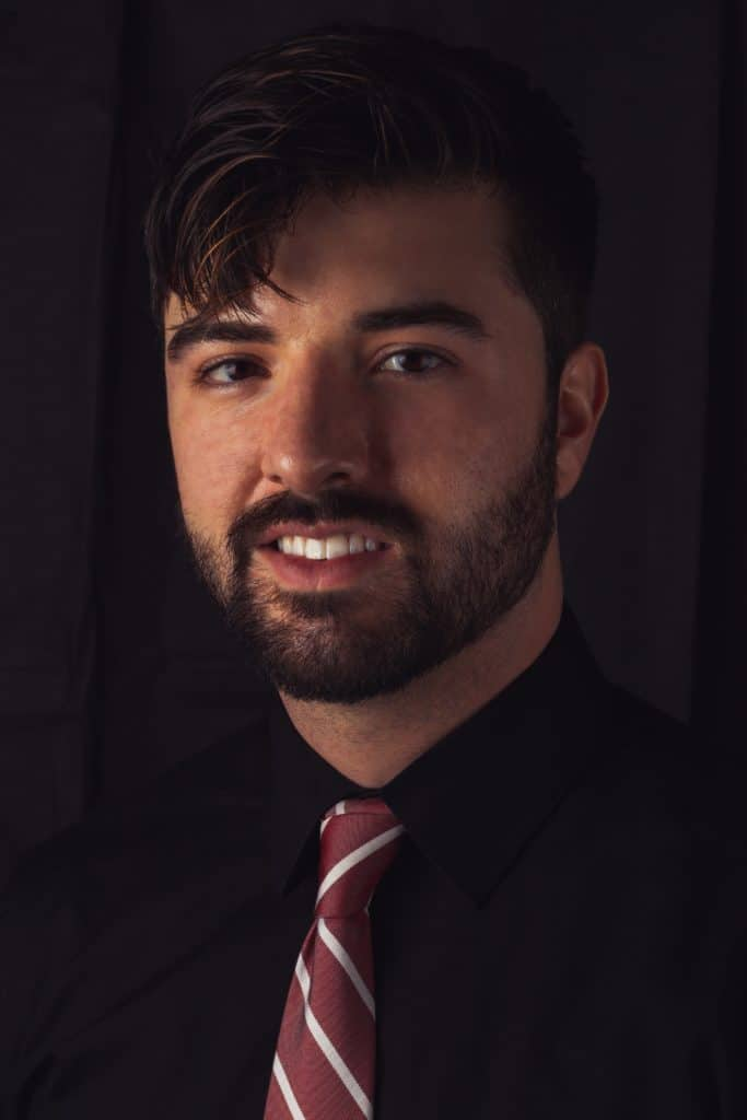 Headshot photo of a gentleman in a black dress shirt and a red/white tie smiling into the camera.